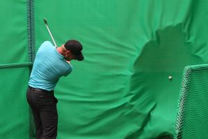 golfer hitting ball into golf baffle net